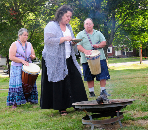 Georgetown: Rev. Debra Adams takes white sage lit by a small fire into an abalone shell as Sherrie Gaudet and Will Langton beat drums. Bryan Eaton/Staff Photo