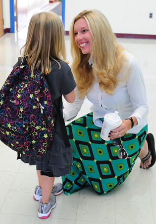 Merrimac: Trisha Etter greets Hilary Young as she enters the Sweetsir School in Merrimac for the first day of school. Etter, an aide at the school, is a friend of Hilary's parents. Bryan Eaton/Staff Photo
