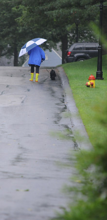 Amesbury: A woman walks her dog down Main Street in Amesbury during a break in the rain Sunday afternoon. Jim Vaiknoras/Staff photo