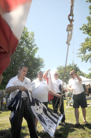 Newburyport: Past Chairmen Dennis Palazzo, Richie Eaton, Don Walters and Jason Lacroix raise the Homecoming flag at Yankee Homecoming's Old-Fashioned Sunday on the Mall.  Jim Vaiknoras/Staff photo