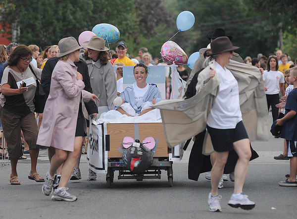 Newburyport: The bed from Woman Heath Care expose themselves as they race a rat themed bed in the Yankee Homecoming Bed Race on Federal Street Thursday night. JIm Vaiknoras/Staff photo