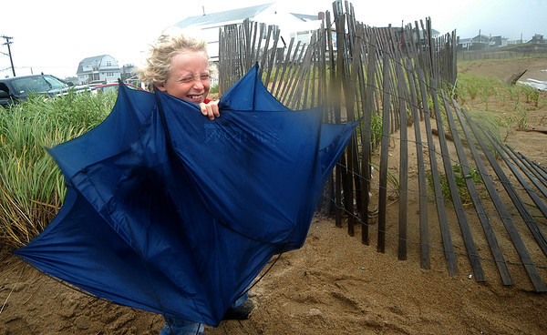 Newbury: Henry Weese of Newburyport uses an umbrella to block the wind as he checks out Hurricane Irene on Plum Island Sunday. The high winds drove not only rain and sea water but sand as well. Jim Vaiknoras/Staff photo