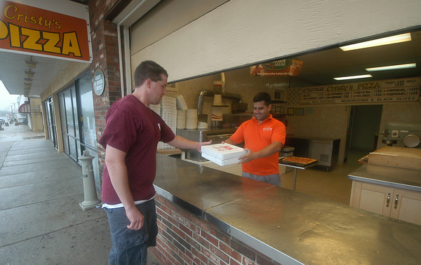 Salisbury: Pat Canny of Rowley picks up a pair of pizzas from Cristy's Pizza on Broadway near Salisbury Beach yesterday afternoon. Canny said he and his fiancee were craving pizza and decided to make the trip despite the stormy weather.<br /> Jim Vaiknoras/Staff photo
