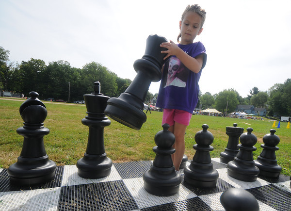 Merrimac: Mackenzie Flanagan, 6, moves her queen in a giant game of chess at Merrimac Old Home Days at the Donahue School Saturday morning. Jim Vaiknoras/Staff photo