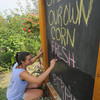 Newbury:Bre Comeau of Amesbury, updates the sign at the Colby Farm on Scotland Rd in Newbury Saturday morning. She was replacing necturine with squash. Jim Vaiknoras/Staff photo