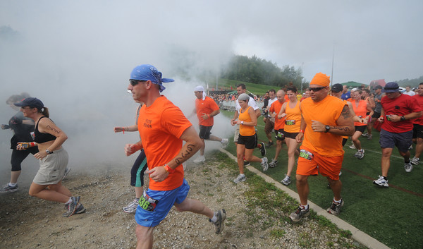 Amesbury:Runners take off through a smoke bomb in the Spatran Race at Amesbury Sports Park Saturday. Jim Vaiknoras/Staff photo