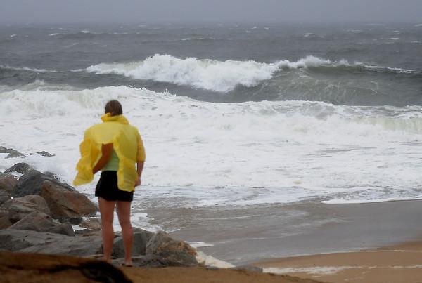 Newbury: High winds blow a woman watching the surf pound Plum Island during Hurricane Irene Sunday. Jim Vaiknoras/Staff photo