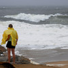 Newbury: High winds blow a woman watching the surf pound Plum Island during Hurricane Irene Sunday. Jim Vaiknoras/Staff photo