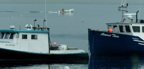 Seabrook: A fisherman moves along some other moored fishing boats on a calm Seabrook Harbor yesterday morning. Bryan Eaton/Staff Photo