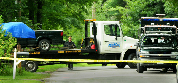 Seabrook: A tow truck removes a green pick-up truck covered with a tarp at 56 Mill Lane which was still blocked off yesterday afternoon as the Major Crimes Unit from the New Hampshire State Police and Seabrook Police investigate the injuries of occupant Michelle Dunn who is in a Boston Hospital. Police have released only limited information on the situation. Bryan Eaton/Staff Photo