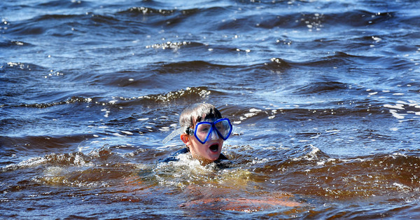 Amesbury: Lucas Brzozowski, 7, of Newburyport and his sister, Juliet, 4, out of view, splash about at Lake Gardner Beach yesterday as wind created strong waves. Bryan Eaton/Staff Photo