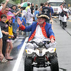 Newburyport: Yankee Homecoming Town Crier Zack Longley rides the paparde on an ATV in the rain Sunday. jim vaiknoras/staff photo