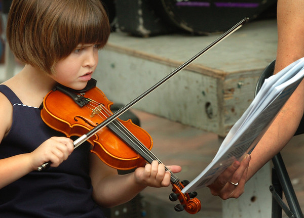Newburyport: Nieve Morrissey, 6, of Newburyport concentrates on her violin as instructor Melinda Rhinelander holds her sheet music. Rhinelander's band, Molly and the Misfits, were playing on Inn Street and at times featured her students' talents. Bryan Eaton/Staff Photo