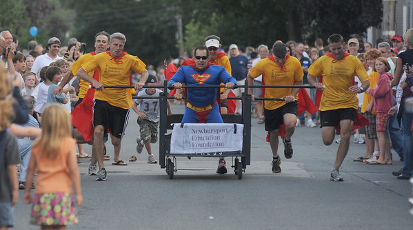 Newburyport: The Newburyport Education Foundation races down a crowded Federal Street in the Yankee Homecoming Bed Race on Federal Street Thursday night. JIm Vaiknoras/Staff photo