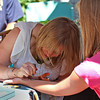 Newburyport: Alyssa Griskiewicz of West Newbury gives young Camren Flury of Londonderry, NH a henna tatoo during Thursday's Yankee Homecoming events in downtown Newburyport. Photo by Ben Laing/Staff Photo