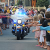 Newburyport: Newburyport policeman Teddy Rice greet the crowd as he rides back up Federal Street to escort the beds in the Yankee Homecoming Bed Race Thursday night. JIm Vaiknoras/Staff photo<br /> , Newburyport: Newburyport policeman Teddy Rice greet the crowd as he rides back up Federal Street to escort the beds in the Yankee Homecoming Bed Race Thursday night. JIm Vaiknoras/Staff photo