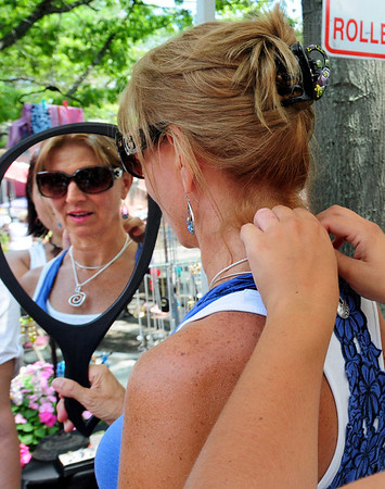 Newburyport: Suzanne Bowman of Haverhill tries on some handmade jewelry with the help of her daughter, Kendra Hayes of Haverhill on Inn Street. The jewelry was made by Nurit Niskala of NuArt in Londonderry, N,H. Bryan Eaton/Staff Photo