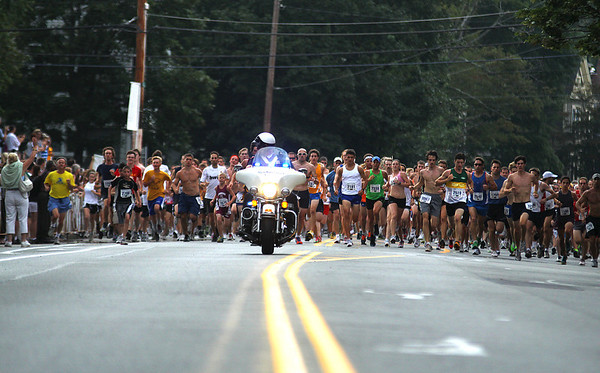 Newburyport: A police escort leads the way as the runners in the 51st annual Yankee Homecoming Road Race take off from the starting line on High Street Tuesday night. Photo by Ben Laing/Staff Photo
