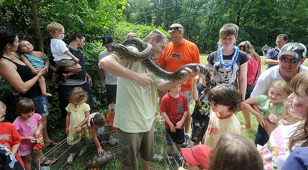 Newburyport:Corey Kumel of Curious Creatures shows off Carlos , a red tail boa, at Family Day at Maudslay Saturday. Jim Vaiknoras/Staff photo
