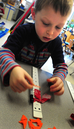 Newburyport: Jake Sherman, 5, puts the nose on his snowman measuring stick in Melissa Duguie's kindergarten class at the Brown School on Monday. The children will be able to use them to check the depth of the winter's snowfall. Bryan Eaton/Staff Photo
