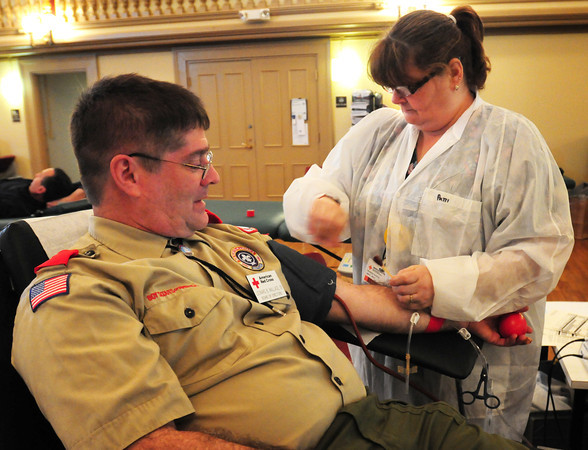 Newburyport: Red Cross worker Patti Pearson takes blood from Newburyport-based Boy Scout Troop 21 leader Leonard B. Wallace IV at Newburyport City Hall on Wednesday. He's also on the Red Cross board of directors which sponsored the blood drive along with the members of the troop who helped register people and provide refreshments for community service part of getting merit badges. Bryan Eaton/Staff Photo
