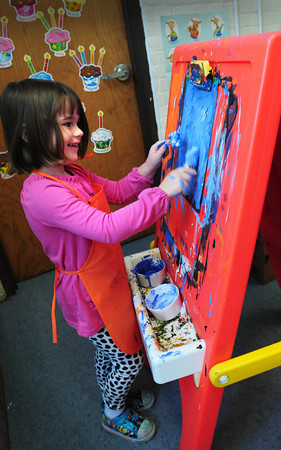 Newburyport: Two-fisted painter Annabel Burkhardt, 3, fills in a page of several stencils of ornaments in Jennifer BIngham's preschool class at the Brown School in Newburyport. The children were learning about all the different holidays of this season.  Bryan Eaton/Staff Photo