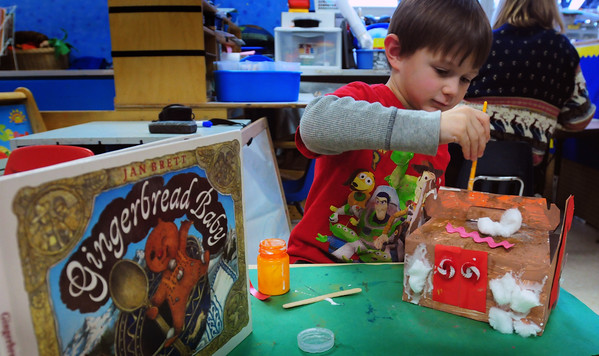 "Amesbury: Quinlan Yescalis, 4, works on a cardboard gingerbread house in  Maryellen Uhlarik's pre-kindergarten class at the Amesbury Elementary School on Wednesday. The children were read the book ""Gingerbread Baby"" before working on their project. Bryan Eaton/Staff Photo"