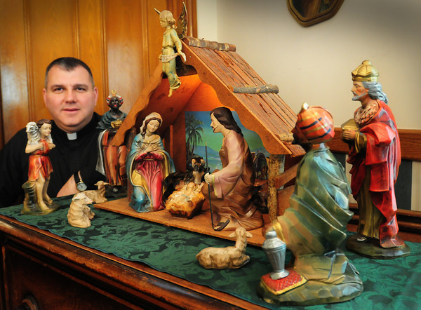 Amesbury: Father Lou Palmeiri with one of his favorite nativity scenes that was owned by his grandparents Anthony and Grace DeLuca. Bryan Eaton/Staff Photo