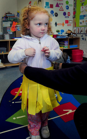 """Newburyport: Teaching aid Joan Locke fits a paper hula skirt onto Allison Miles, 3, at the Brown School in Newburyport on Tuesday morning. They children will be performing in a Winter Concert next week as the """"Merry Hulas."""" Bryan Eaton/Staff Photo"""