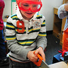 Salisbury: Connor Gray, 4, pretends to be a carpenter learning safety by wearing goggles while pretending to saw a piece of wood. The youngster was in play time in Julie Deshene's preschool class at Salisbury Elementary School on Monday morning. Bryan Eaton/Staff Photo