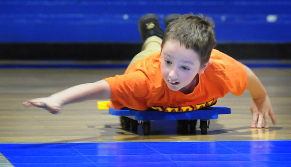Salisbury: Nicholas Lindley, 10, glides along the gym floor at the Boys and Girls Club on Tuesday afternoon. He and several friends were competing in scooter races. Bryan Eaton/Staff Photo