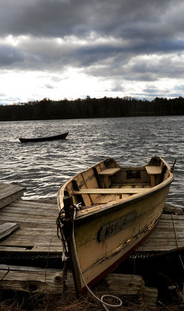 Amesbury: Though one boat is in the water at Lowell's Boat Shop in Amesbury, the choppy waves of the Merrimack River and ominous sky assures one that boating season is long over. Bryan Eaton/Staff Photo