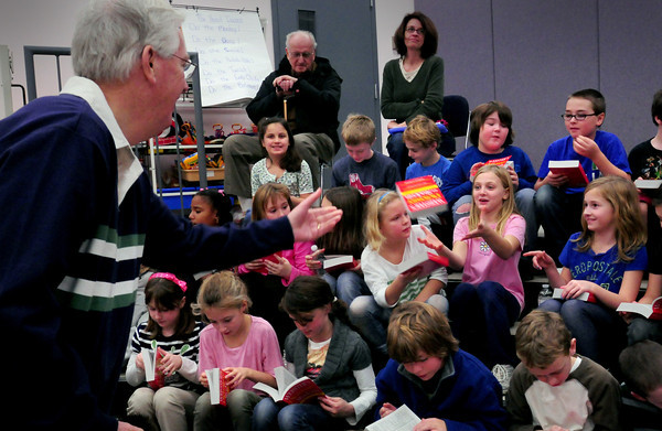 Amesbury: Amesbury Rotarian tosses dictionaries to third-graders seated up in the Little Theater at the Cashman School on Tuesday. The group gives the books once a year and later in the day presented some at Amesbury Elementary School. Bryan Eaton/Staff Photo