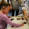 Salisbury: Kathleen Orroth's Kindergarten made cinnamon gingerbread men that will be dried as ornaments, with the help of parent volunteers, to give to each other as gifts. Erin Story helped Martha Snow, 5, signing her name, make hers. Bryan Eaton/Staff Photo