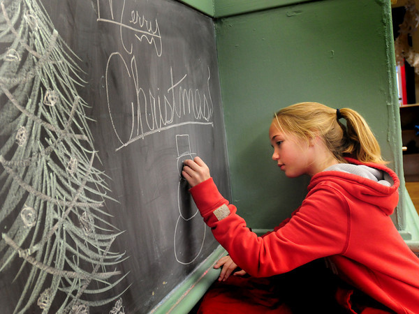 Newburyport: Ava Gridley, 11, creates some seasonal artwork on the blackboard in one of the classrooms at the Kelley School Teen Center. She likes to create artwork and hopes to get better at it. Bryan Eaton/Staff Photo