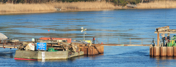 Amesbury: A construction worker on the center pier of the Hines Bridge, which is being rebuilt, monitors the placement of concrete yesterday afternoon, in a view from the side of the Whittier Bridge. Bryan Eaton/Staff Photo