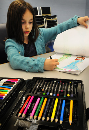 Salisbury: Felicia MacDonald, 6, of Amesbury, who considers herself an artist, draws two fashion models in her sketcbook at the Boys and Girls Club. The got the art kit in foreground for Christmas. Bryan Eaton/Staff Photo