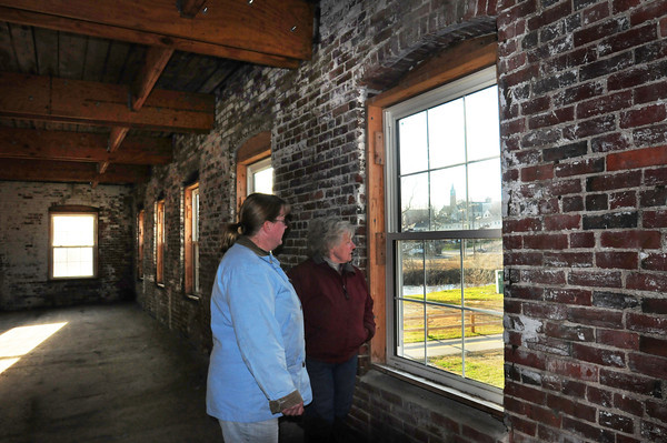 Amesbury: Carriage Museum member Janet Sawyer, left, and board president Ann Miles look at the Powow River through one of the windows of the as yet opened museum building. Bryan Eaton/Staff Photo
