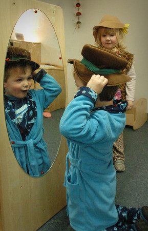 Newburyport: Nathanial Hackett, 4, in mirror, and Sienna Schwartz, 3, goof off  with different hats at the Newburyport Montessori School yesterday morning during playtime. They were having Pajama Day as they get out of school today for the Christmas break. Bryan Eaton/Staff Photo