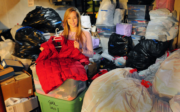 Newburyport: Lauren Sundstrom is surrounded by several dozens of bags and tubs of clothing in the cellar of a friend's home to handle the overflow of items she's collected. The Newburyport High student is planning to sell the clothers, many of them designer, to raise money to help out children in Africa. Bryan Eaton/Staff Photo