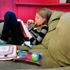 "Newburyport: Emma Fisher, 11, relaxes on a big couch while others do crafts or outside in the playground at the Kelley School Youth Center. She was reading  ""Eldest"" about a person who has a dragon. Bryan Eaton/Staff Photo"
