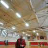 AMESBURY: Brad Ford, the Director of Operations for Amesbury Public Schools, stands under the new energy efficiant lights in the gym at Amesbury high. Jim Vaiknoras/staff photo