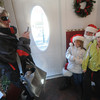 Newburyport: Samantha Protopapas, 7 along with her sister Samantha , 10, pose with Santa at his Inn Street workshop as their mom Deb takes a photo with her phone. Jim vaiknoras/staff photo