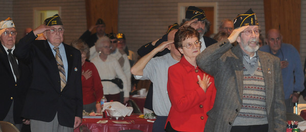 Amesbury : Veteran's and their families salute the flag during the Pleadge of Allegiance at the 11th annual Support the Troops Christmas Dinner at the Holy Family Parish Hall in Amesbury Thursday night. Jim Vaiknoras/staff photo