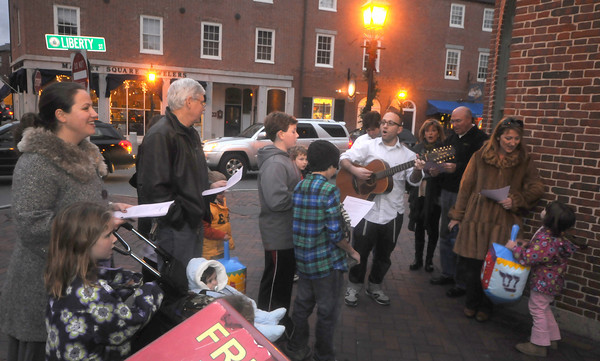 Newburyport: Rabbi Avi Poupko of the Congregation Ahavas Achim leads the first Chanukah Caroling on the corner of Librerty and State Streets in  Newburyport Thursday night. Along with singing at different location downtown the group passed out gelt, chocolate coins, to those who came to listen.JIm Vaiknoras/staff photo