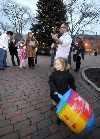 Newburyport: Judah Poupko swings a giant inflatable dreidle as his father Rabbi Avi Poupko of the Congregation Ahavas Achim leads singers during the first Chanukah Caroling in Market Square Thursday night. Along with singing at different location downtown the group passed out gelt, chocolate coins, to those who came to listen.JIm Vaiknoras/staff photo