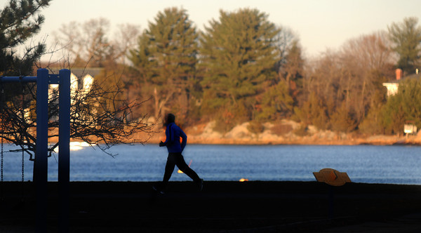 Newburyport: A runner makes his way through Cashman Park in Newburyport along the Merrimack River in the late afternoon Thursday. Jim Vaiknoras/staff photo