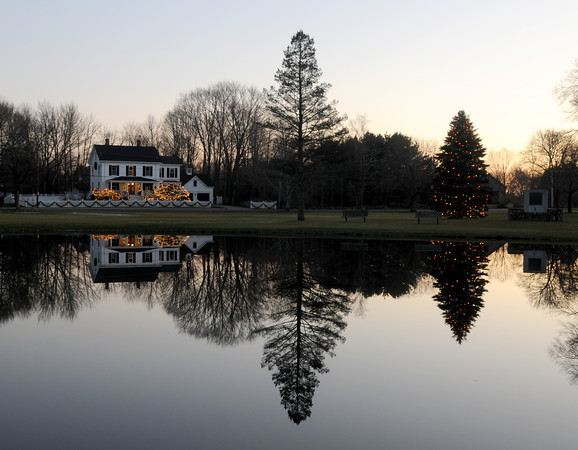 Newbury: Pine trees and holiday lights are relcted in the still pond on the Upper Green in Newbury. staff photo