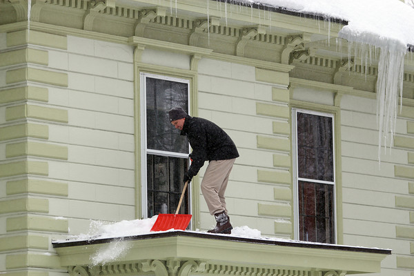 Newburyport: Seth Harris shovels off the roof above the entry way of his house on High Street Wednesday afternoon during the latest snow storm. Photo by Ben Laing/Staff Photo