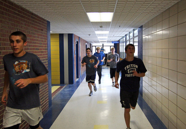 Byfield: Members of the boys indoor track team at Triton run through the hallways during Monday afternoon's practice. Photo by Ben Laing/Staff Photo